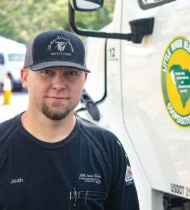 """LREC's Josh Strickland wearing a """"Safety First"""" cap and standing next to a Little River truck."""