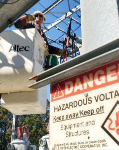 Crew member in truck bucket tending to power lines