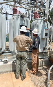 New Horizon crew members inspecting a power transformer.