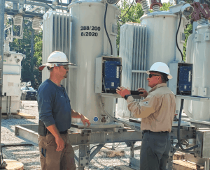 Pictured: Bret Timmerman (left) and Michael Hall install a new program to a substation regulator.