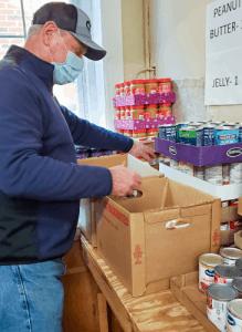 Volunteer packs food boxes in photo